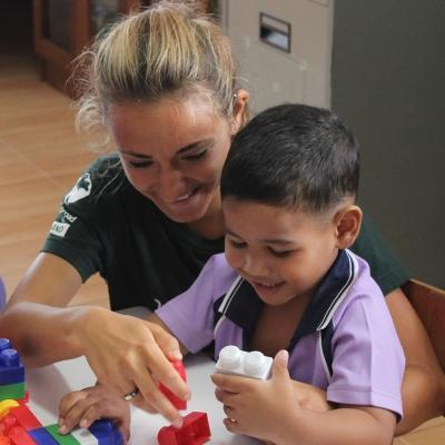 A volunteer working abroad with children spends time building blocks with a child to improve early childhood development.